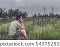 Young man in casual clothing sitting in a meadow 54375203