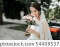 Smiling beautiful young bride with bouquet of flow 54409537