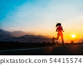 Young woman enjoys running on road. 54415574