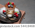 Classic tiramisu dessert with blueberries and raspberries in a glass on dark concrete background 54419468