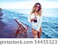 Pretty woman relaxing on beach and drinks coctail. summer vacation concept 54435323