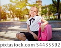 Pupil of primary school sitting on stairs put her hand on the briefcase and looking at the camera 54435592