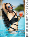 Tenned beautiful woman in orange bikini and sunlasses sitting in swimming pool with cocktail 54436091