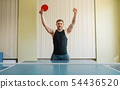 Man with ping pong racket raised his hands up 54436520