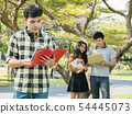 Handsome young college student holding books and 54445073