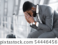 Depressed Man Sitting at Airport with Baggage 54446456