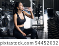Sporty girl drink water after dumbbell exercise 54452032