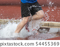 Runner in a steeple chase water bake on a running 54455369