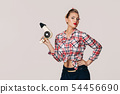 Happy young brunette woman with hair dryer. 54456690