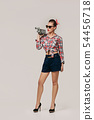 pin-up girl in plaid shirt holding old vintage camera. 54456718