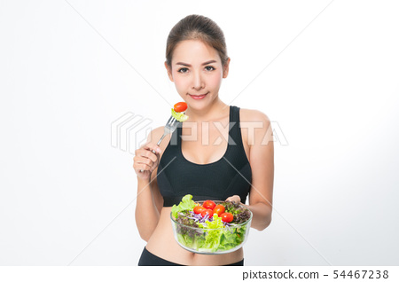 Girl in a fitness suite holds a salad bowl. 54467238