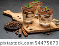 Classic tiramisu dessert with chocolate in a glass no wooden cutting boartd on dark concrete 54475673