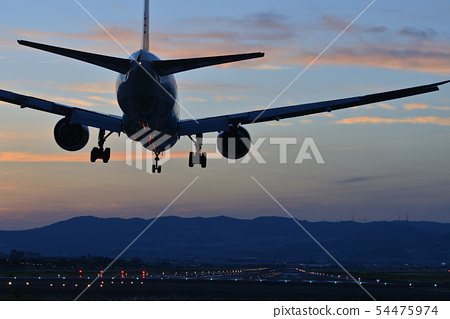 Airliner ready for landing during sunset 54475974