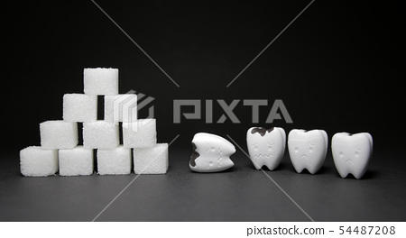 Heap of a lot of cubes sugar and Decayed tooth  54487208