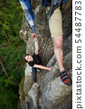 Happy woman climbing rock trekking outdoors. Carefree hiker smiling her friend. Friendly helping 54487783