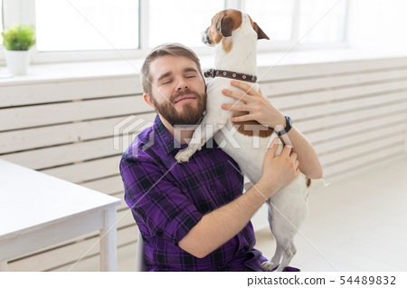 people, pets and home concept - young man playing with jack russell terrier puppy on white 54489832