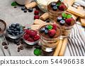 Classic tiramisu dessert with blueberries and raspberries in a glass and savoiardi cookies on 54496638