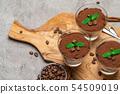 Classic tiramisu dessert in a glass cup on wooden cutting board on concrete background 54509019