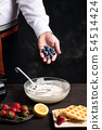 Chef adding fruit in waffles dough 54514424