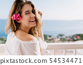 Cheerful laughing girl with cute flower in light 54534471
