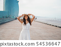 Pretty woman wearing white dress and pamela hat standing 54536647