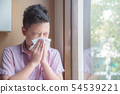 Sick asian boy blowing nose into tissue 54539221