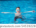 Happy boy wearing goggles and swimming at pool 54539228