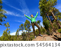 Hiking woman reaching summit cheering in forest 54564134