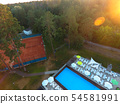 Aerial view beautiful summer pool with sunbed and tennis courts parasols and at a country recreation 54581991