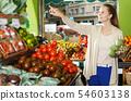 woman who is choosing artichokes 54603138