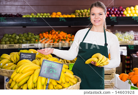 Young female in apron selling fresh bananas on the market 54603928
