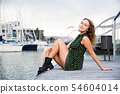 Sexy girl in dress sitting at quay with boats on background in Barcelona 54604014