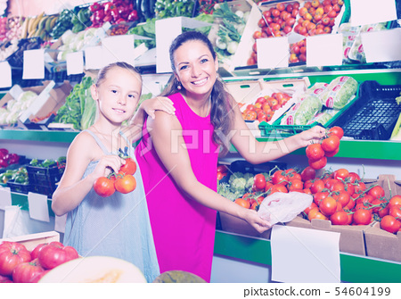 young woman with daughter buying tomatoes. 54604199