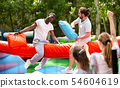 Cheerful pillow fight sitting on a log in an amusement park 54604619