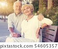 couple of male and female sitting on bench 54605357