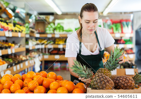 Young woman wearing apron working with fresh pineapples 54605611