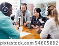 Radio hosts interviewing guest 54605892