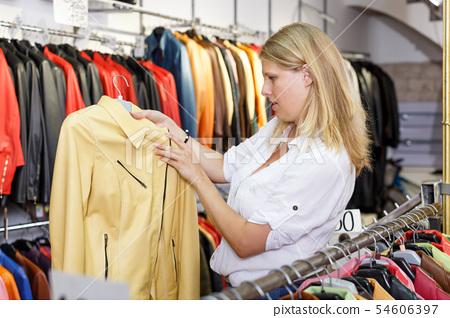 Woman choosing leather jacket 54606397