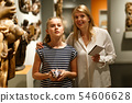 Woman with girl holding guidebook, standing in museum of ancient sculpture 54606628