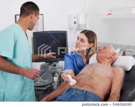 Woman and man doctors examines a senior man at abdomen 54606690