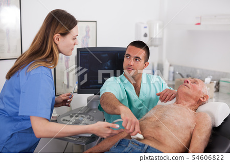 Woman and man doctors with ultrasonography device, examination man 54606822