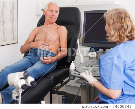 doctor examines a senior man with ultrasonic device 54606845