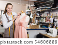 Woman worker measuring new dress at mannequin at atelier 54606889