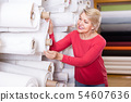 aged woman customer looking for beautiful fabric in textile shop 54607636
