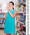 Attractive female want to buying softener in bottle 54608323