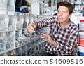 Smiling male in hardware shop buying goods 54609516