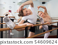 Teenager and women practicing at the ballet barre 54609624