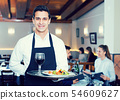 Smiling waiter with serving tray 54609627