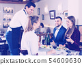 Waiter bringing dishes to guests 54609630