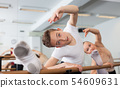 Graceful woman and young man pose in hall with ballet bar 54609631